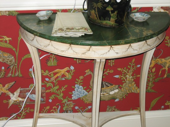 A faux painted demi-lune table highlights the wallpaper